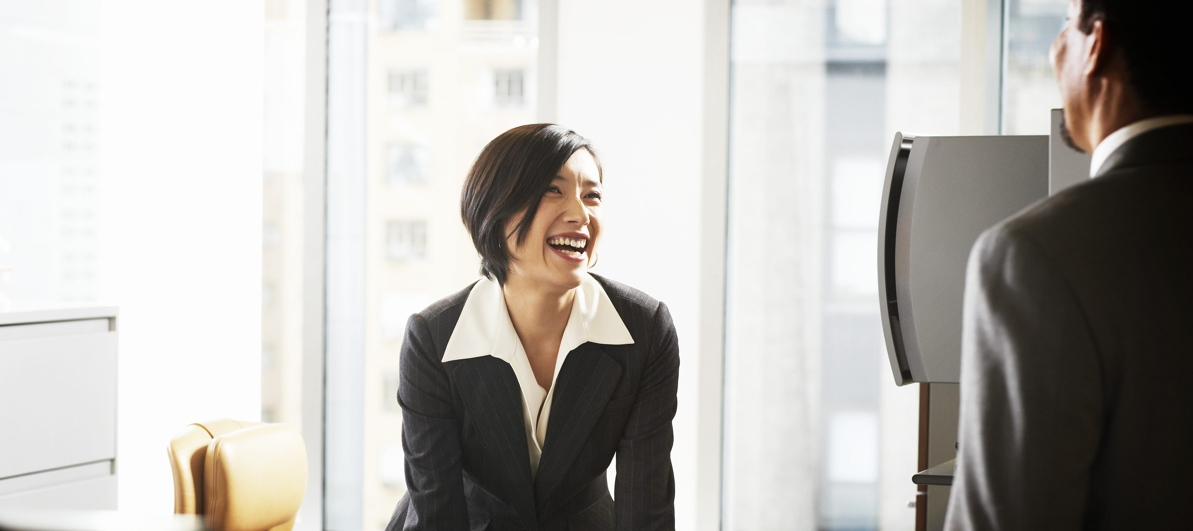 Businesswoman at desk smiiling at businessman