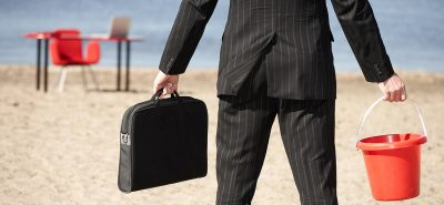 Businessperson with sand pail and briefcase