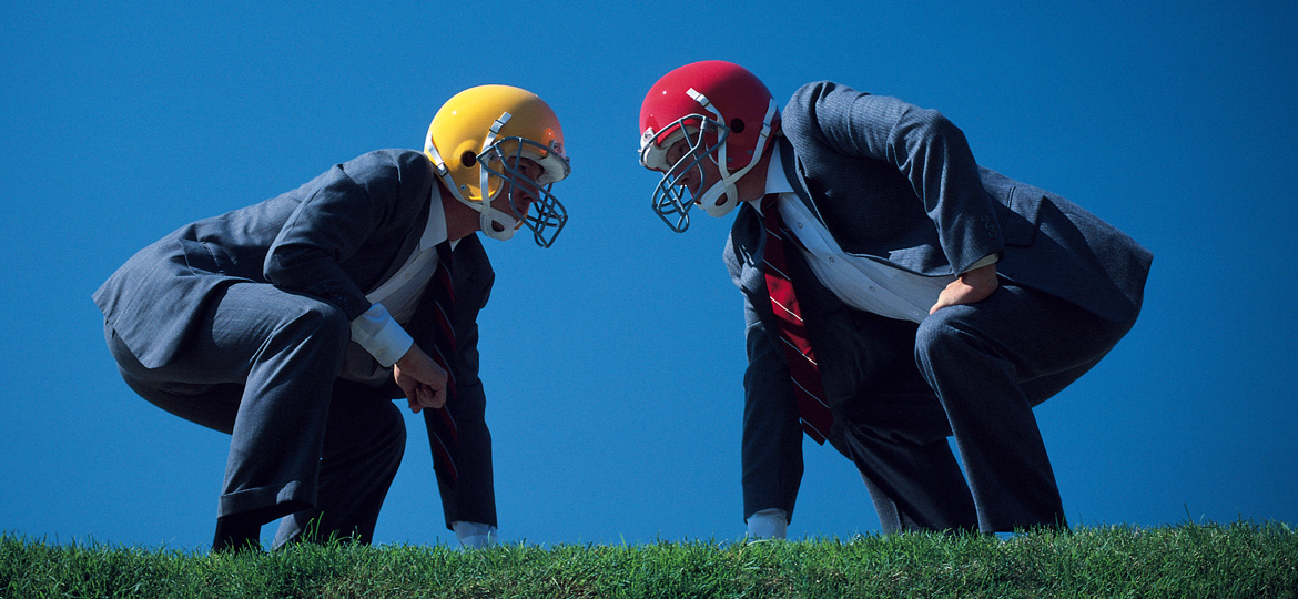 Businessmen wearing football helmets go head to head