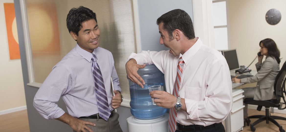 Men standing at water cooler in office