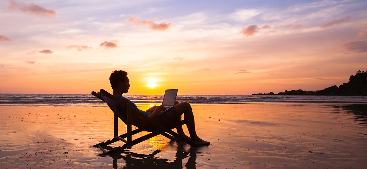 Man working on laptop at beach