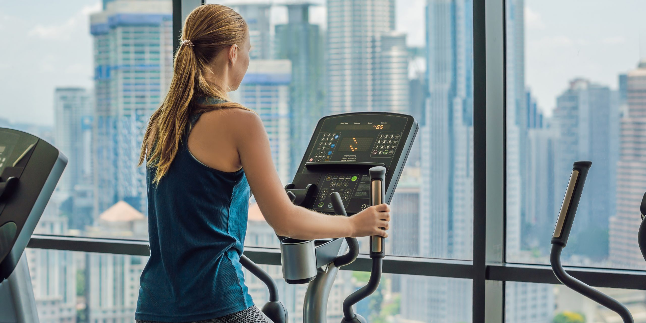 Woman exercising on an elliptical in a multi-family building